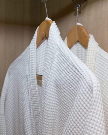 white bathrobes hanging in wooden closet